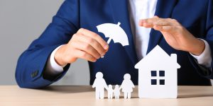 Männlicher Versicherungsvertreter, der Papierfamilie und Haus mit Schirm am Tisch bedeckt, Nahaufnahme