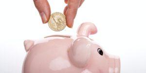 Münze wird in Sparschwein gesteckt