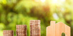Geldstapel und Holzhaus